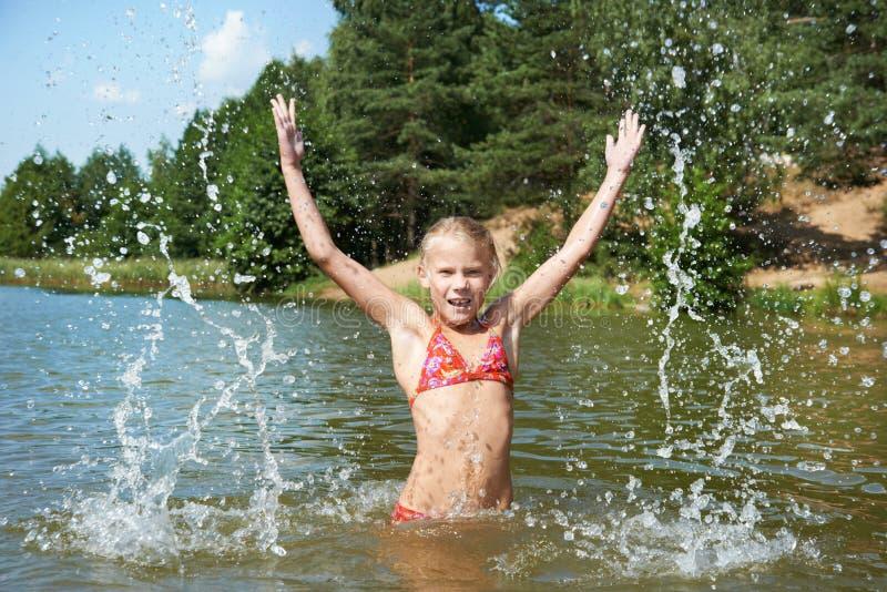 Liten flicka i vatten och sprej royaltyfria foton