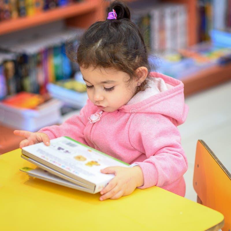 Liten flicka inomhus i Front Of Books Gulligt ungt litet barn som sitter p? en stol n?ra tabellen och l?seboken Arkivet shoppar arkivbilder