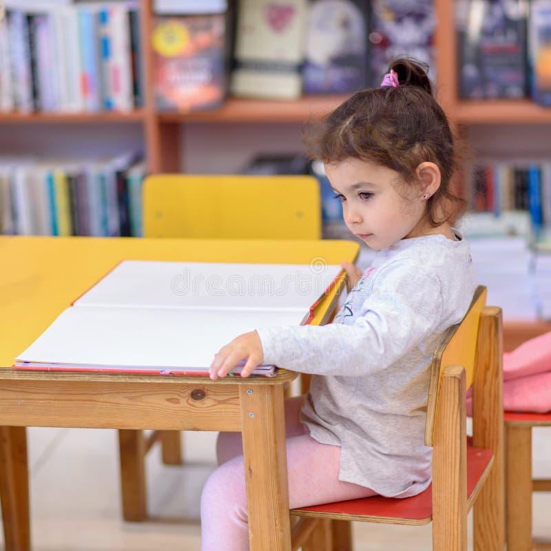 Liten flicka inomhus i Front Of Books Gulligt ungt litet barn som sitter p? en stol n?ra tabellen och l?seboken arkivbild