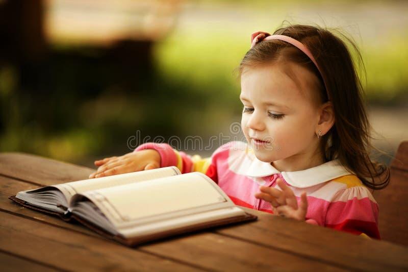 Liten flicka läser bokar royaltyfria bilder