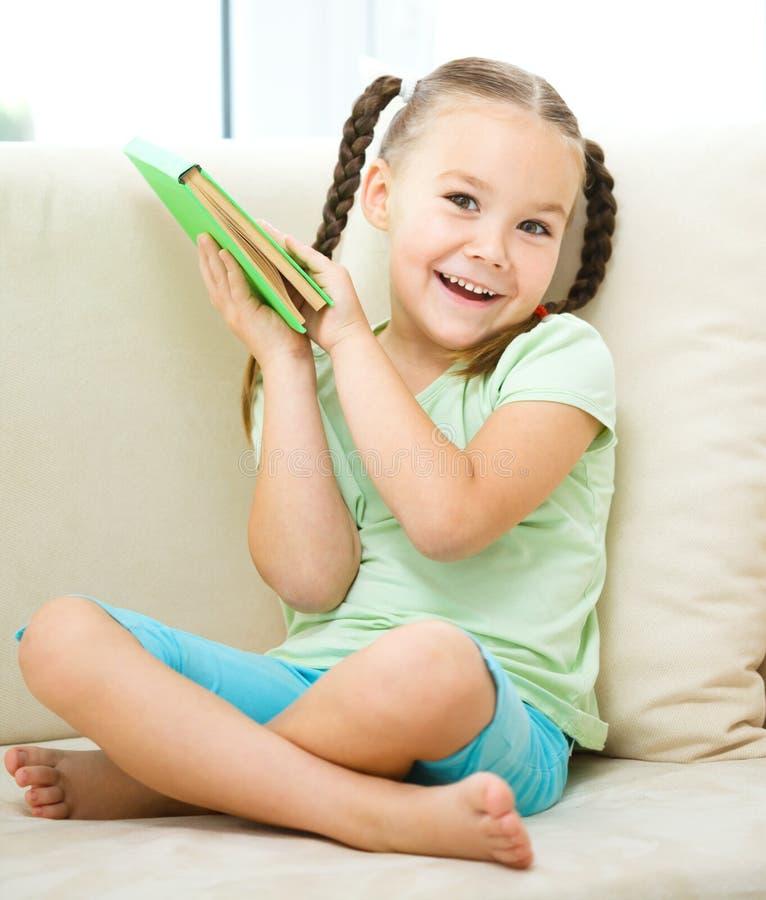 Liten flicka läser en bok royaltyfri fotografi