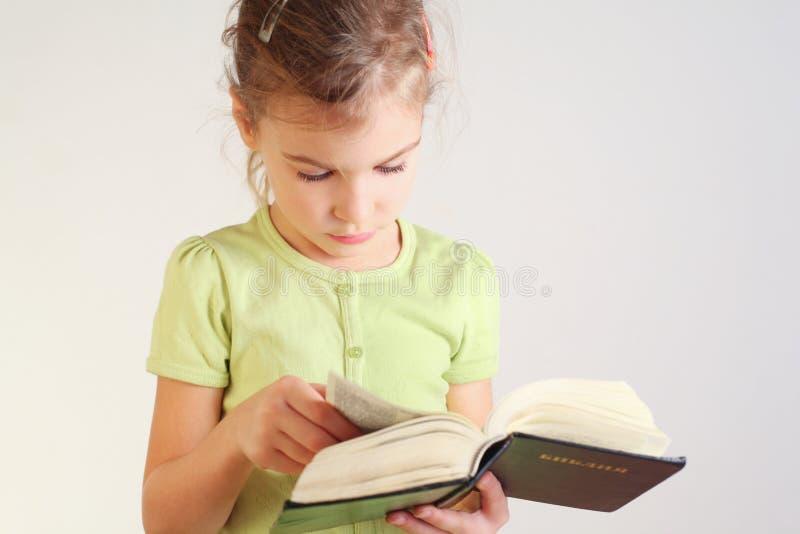 Liten flicka läste bibeln arkivbilder