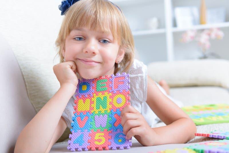 Liten flicka med alfabetpusslet arkivfoton