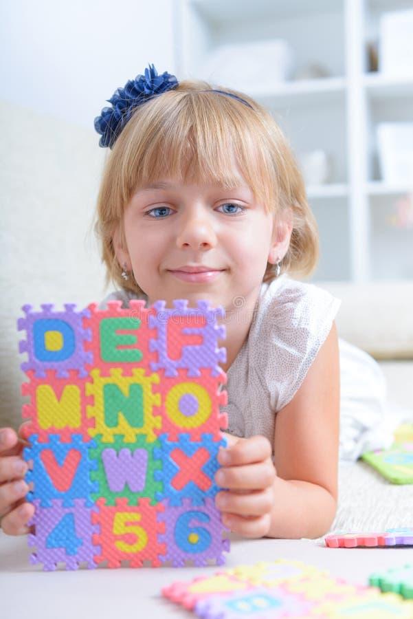 Liten flicka med alfabetpusslet arkivfoto