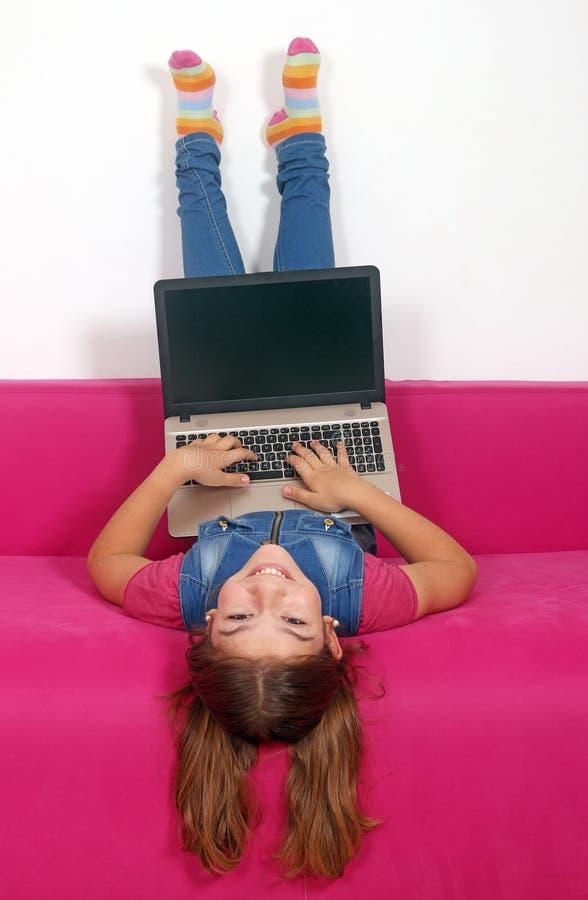 Liten flicka med att ligga för bärbar dator som är uppochnervänt på säng fotografering för bildbyråer