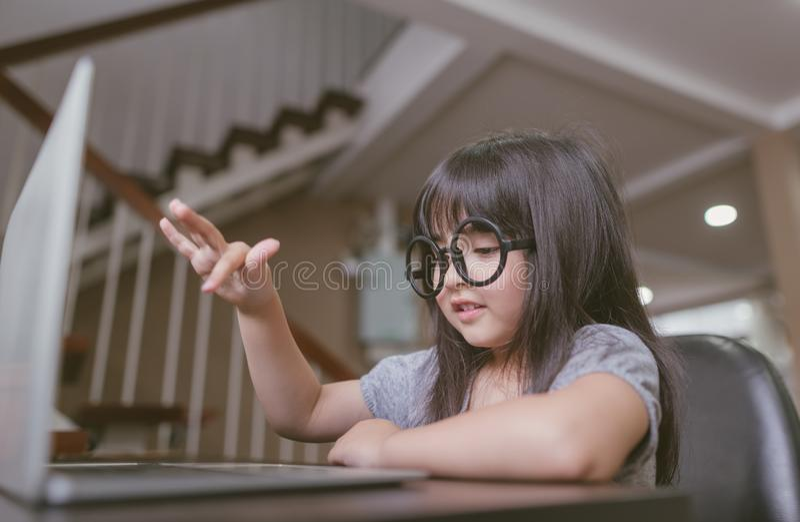 Liten flicka med bärbar datorarbete hemma royaltyfri foto