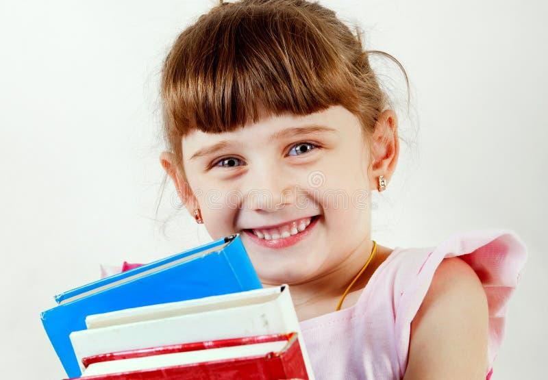 Liten flicka med böcker arkivbilder