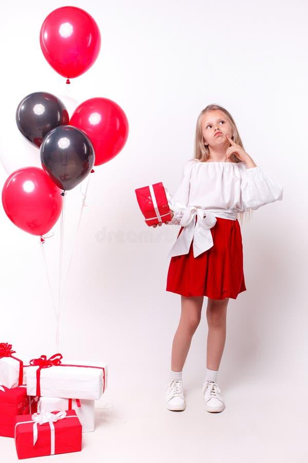 Liten flicka med ballonger och gåvor arkivfoto