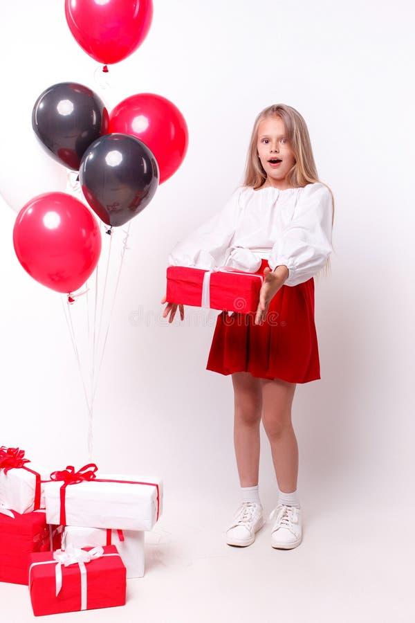 Liten flicka med ballonger och gåvor royaltyfri fotografi