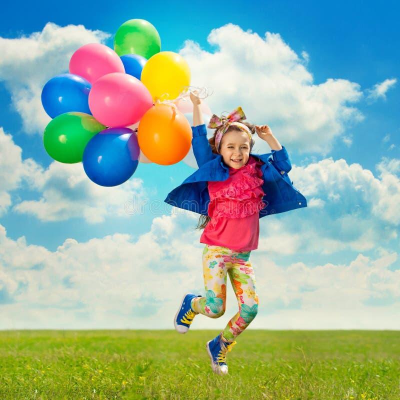 Liten flicka med ballonger som hoppar på fältet royaltyfria foton
