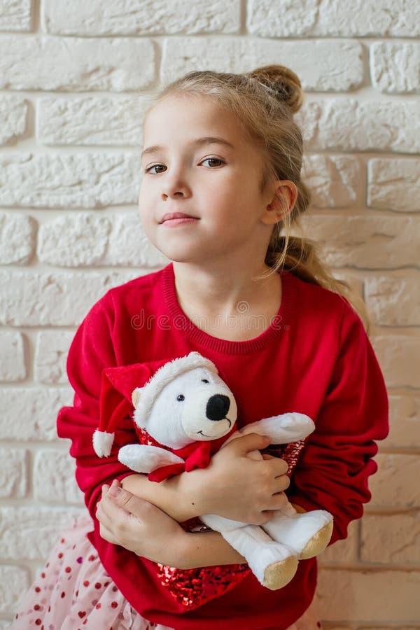 Liten flicka med björnleksaken framme av jul arkivfoton