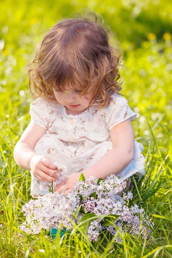 Liten flicka med blommor arkivbilder