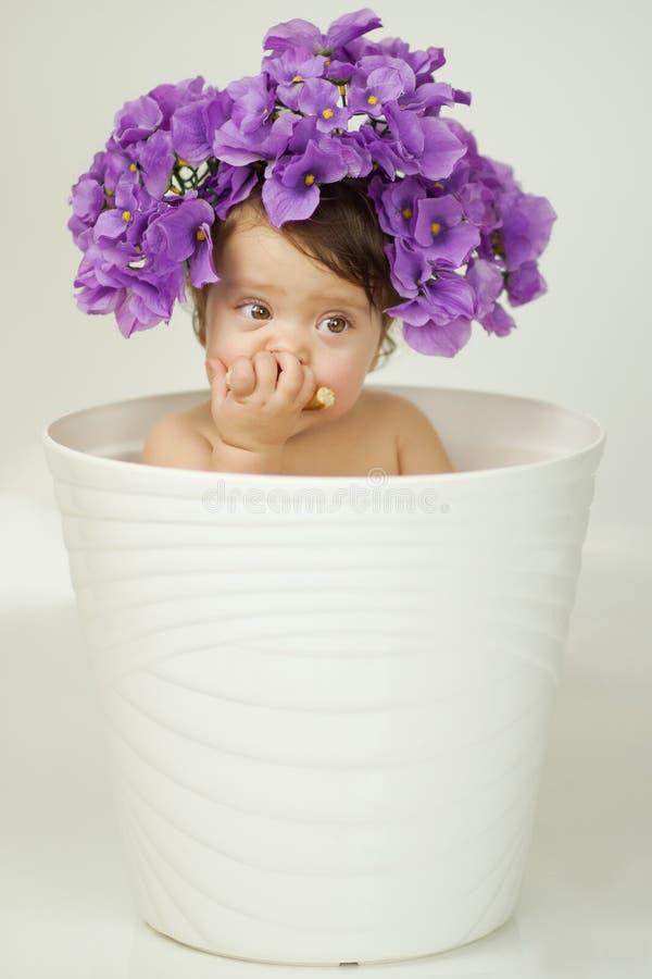 Liten flicka med blommor på hennes huvud arkivfoton