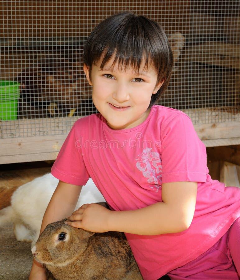 Liten flicka med brun kanin fotografering för bildbyråer