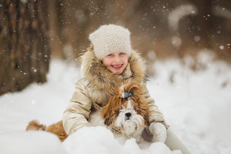 Liten flicka med den älsklings- hunden för en gå fotografering för bildbyråer