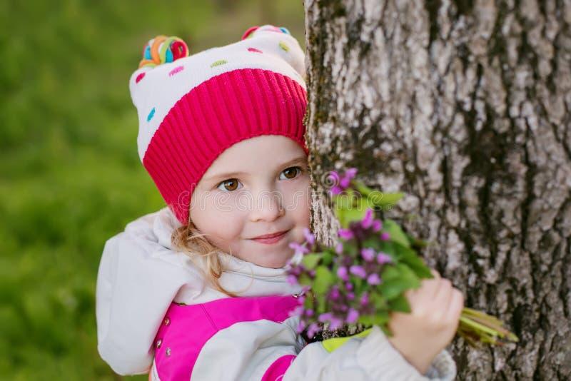 Liten flicka med den blom- buketten i skogsmark fotografering för bildbyråer