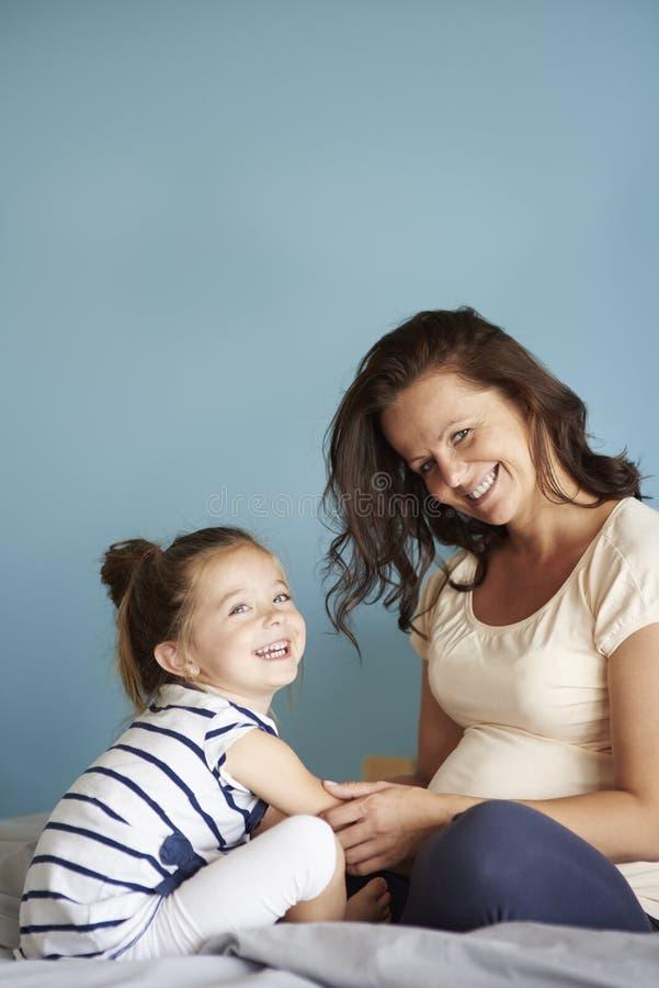 Liten flicka med den gravida mamman arkivbilder