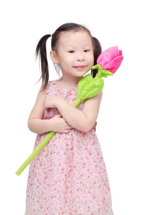 Liten flicka med den konstgjorda rosblomman fotografering för bildbyråer