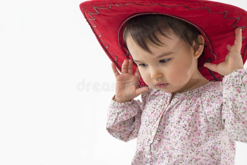 Liten flicka med den röda cowboyhatten som isoleras på vit royaltyfria bilder