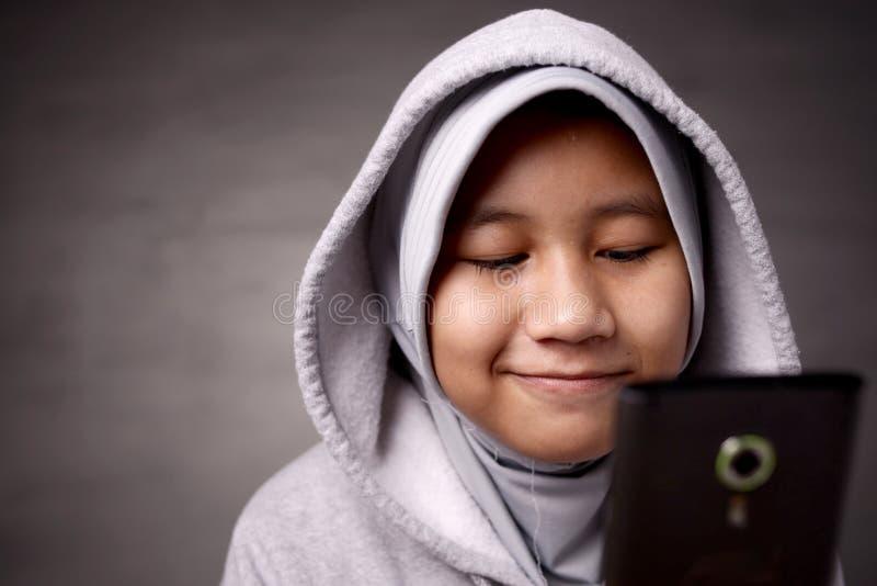 Liten flicka med den smarta telefonen royaltyfria foton