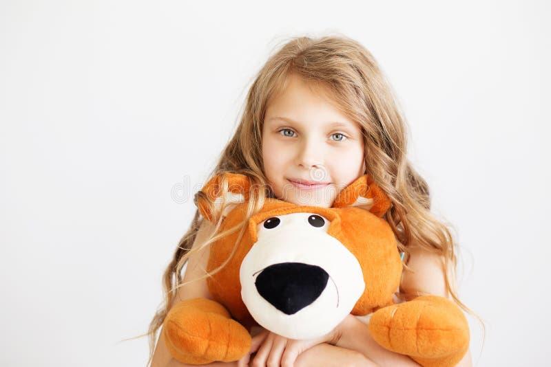 Liten flicka med den stora nallebjörnen som har att skratta för gyckel att isoleras på royaltyfri foto