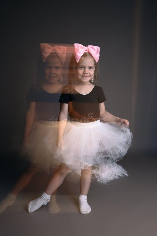 Liten flicka med den stora pilbåge- och balettballerinakjolen royaltyfri fotografi