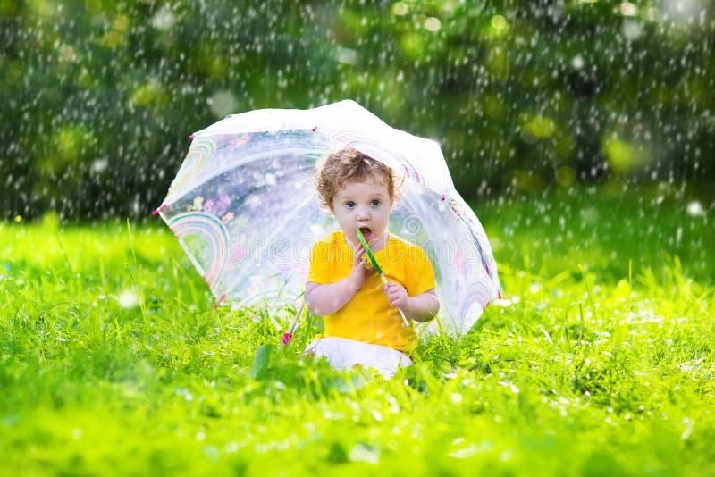 Liten flicka med det färgrika paraplyet som spelar i regnet royaltyfria foton
