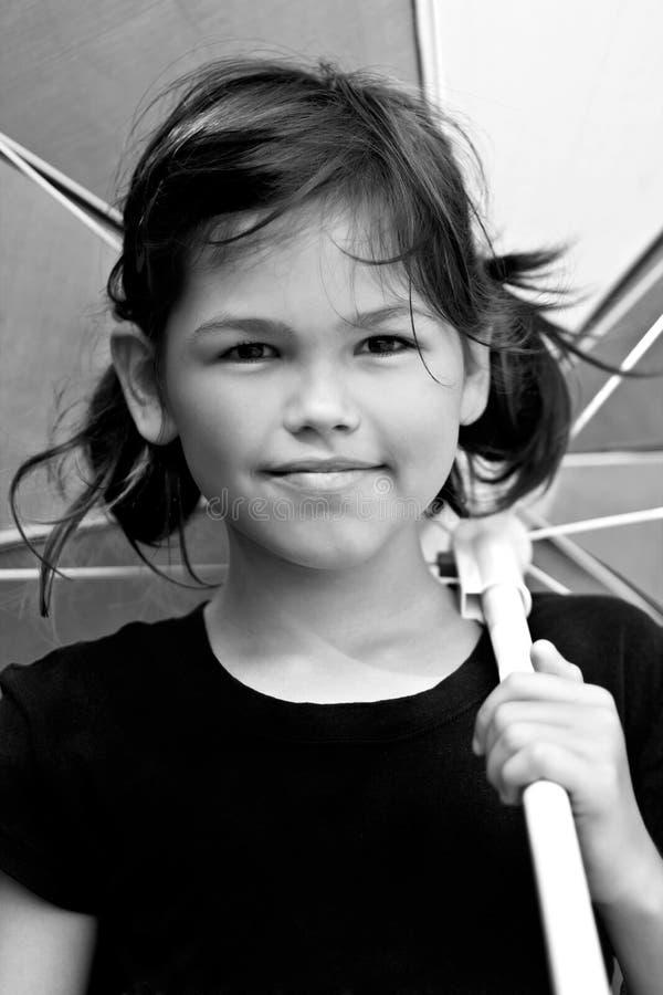 Liten flicka med det stora färgrika paraplyet arkivfoto