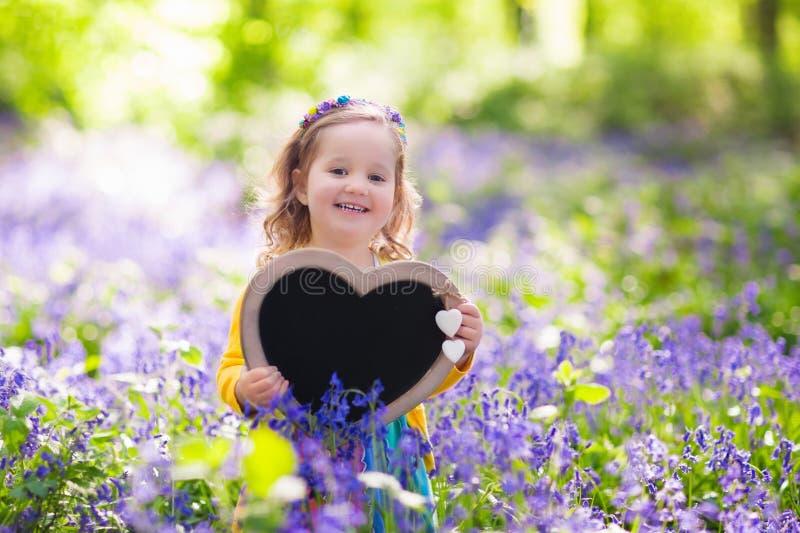 Liten flicka med det tomma brädet i blommafält royaltyfria foton
