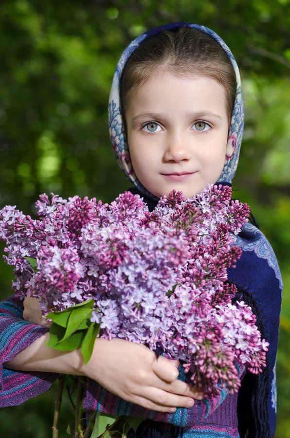Liten flicka med en bukett av en blomstra lila i hand royaltyfri foto