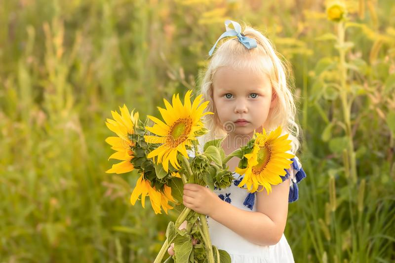 liten flicka med en bukett av solrosor fotografering för bildbyråer