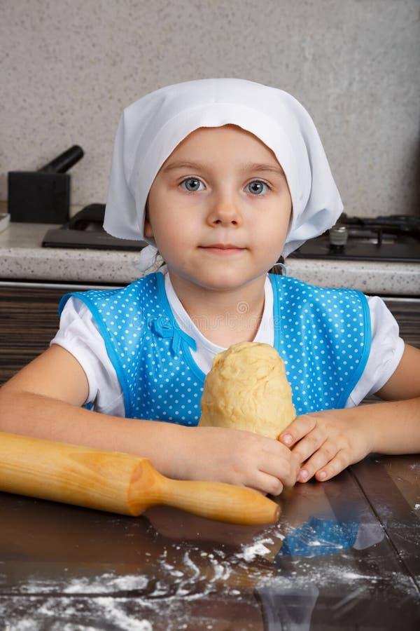 Liten flicka med en deg i ett kök royaltyfri fotografi