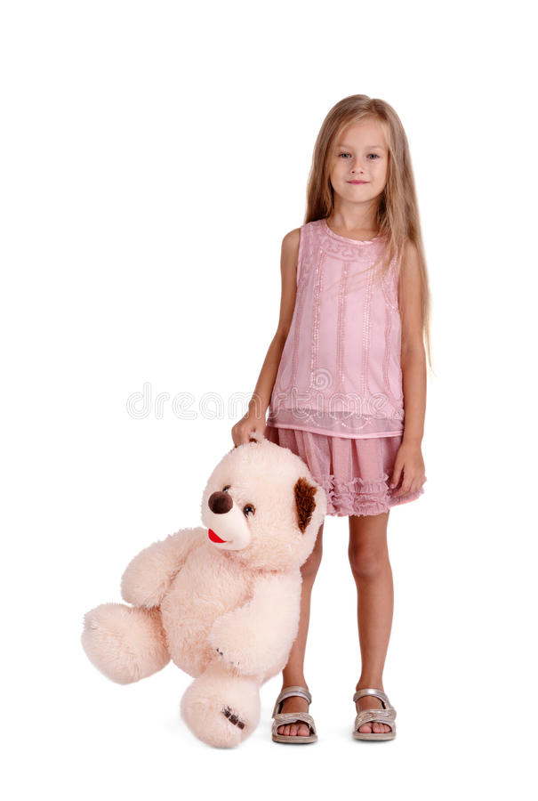 Liten flicka med en flott leksak som isoleras på en vit bakgrund Smart unge med en nallebjörn Barndombegrepp kopiera avstånd arkivfoton