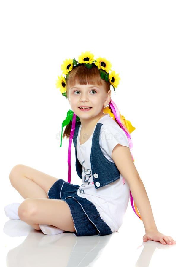 Liten flicka med en h?rlig krans av blommor p? hennes huvud royaltyfri bild