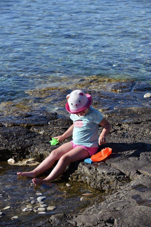 Liten flicka med en hatt som spelar på stranden arkivbilder