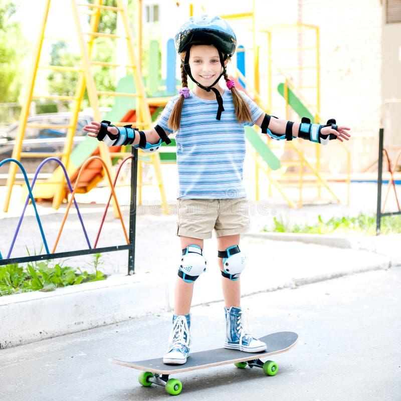 Liten flicka med en hjälmridning på skateboarden royaltyfri fotografi