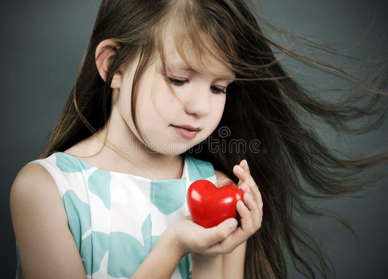 Liten flicka med en hjärta arkivbild