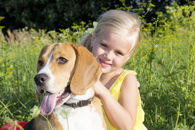 Liten flicka med en hund fotografering för bildbyråer