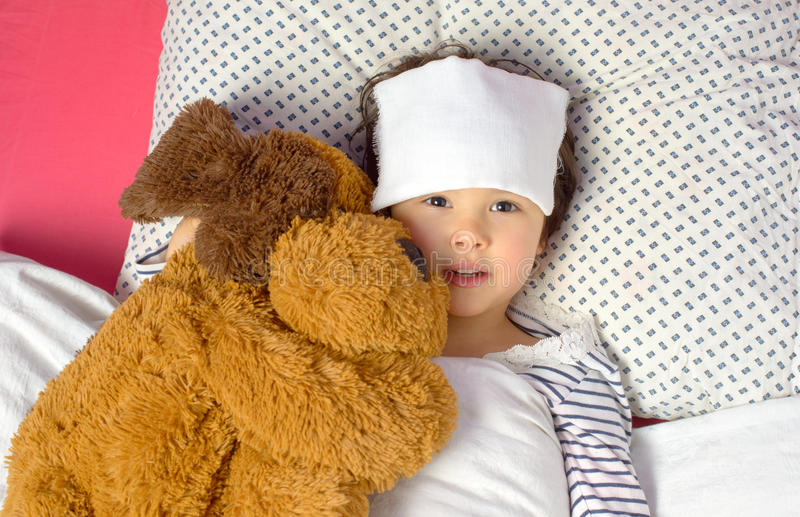 Liten flicka med en huvudvärk i säng royaltyfri bild