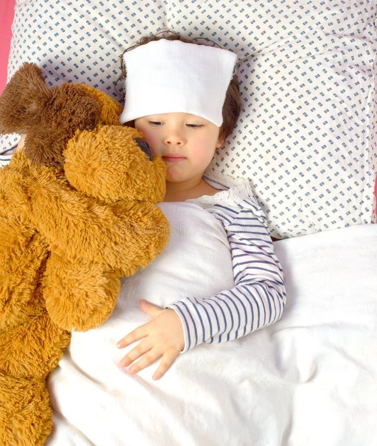Liten flicka med en huvudvärk i säng royaltyfri fotografi