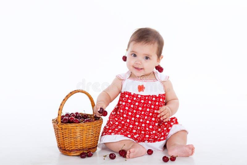 Liten flicka med en korg av att äta körsbär arkivbilder