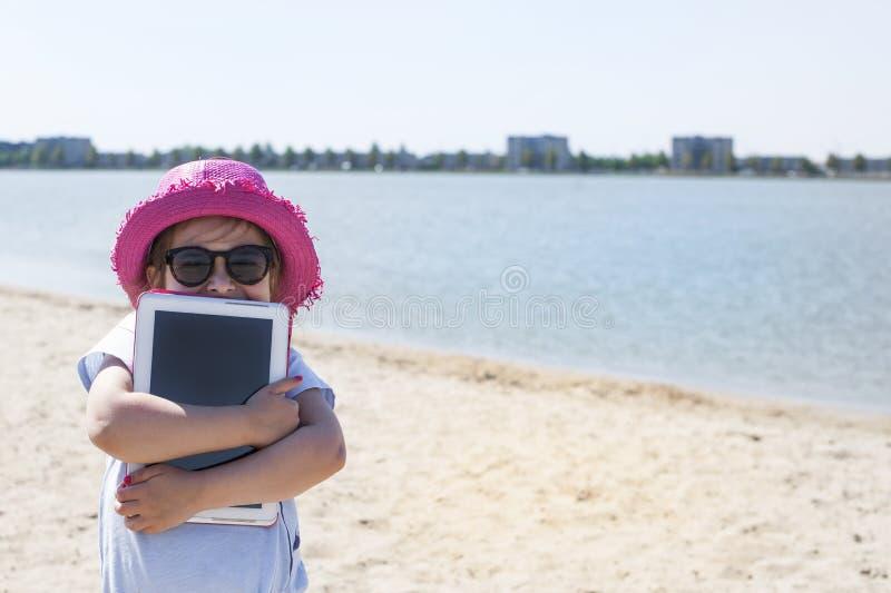 Liten flicka med en minnestavladator i händer Bra sommarhelg på stranden kopieringsspce arkivfoto