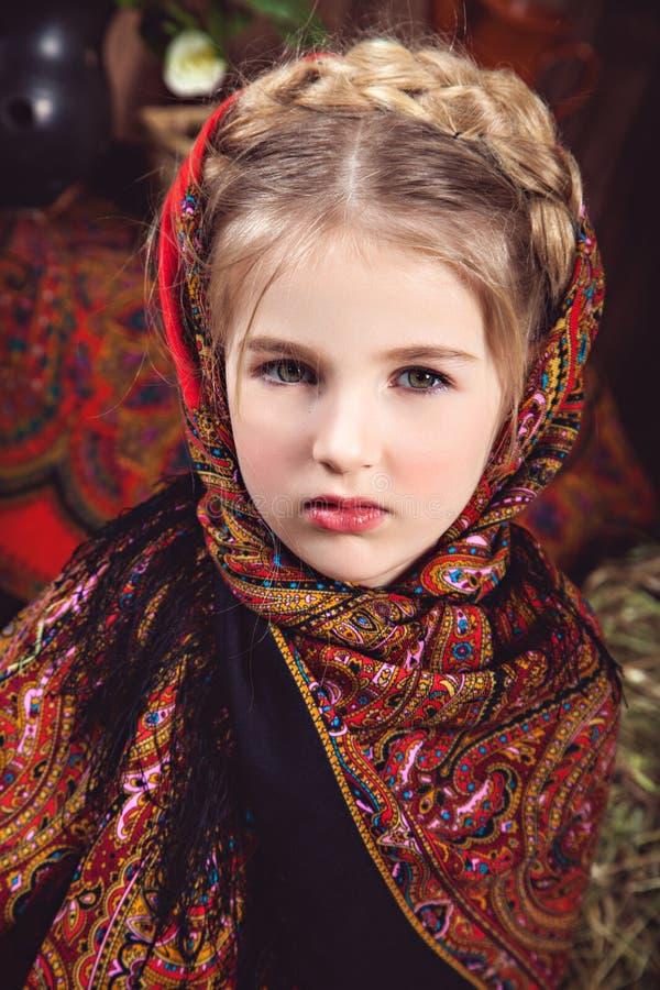 Liten flicka med en råttsvans i kulör sjalett arkivfoto