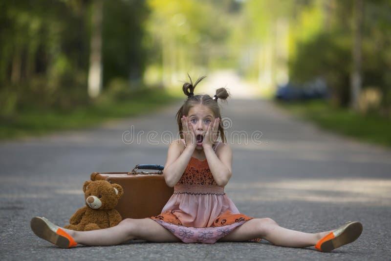 Liten flicka med en resväska och en nallebjörn som sitter på vägen royaltyfri foto