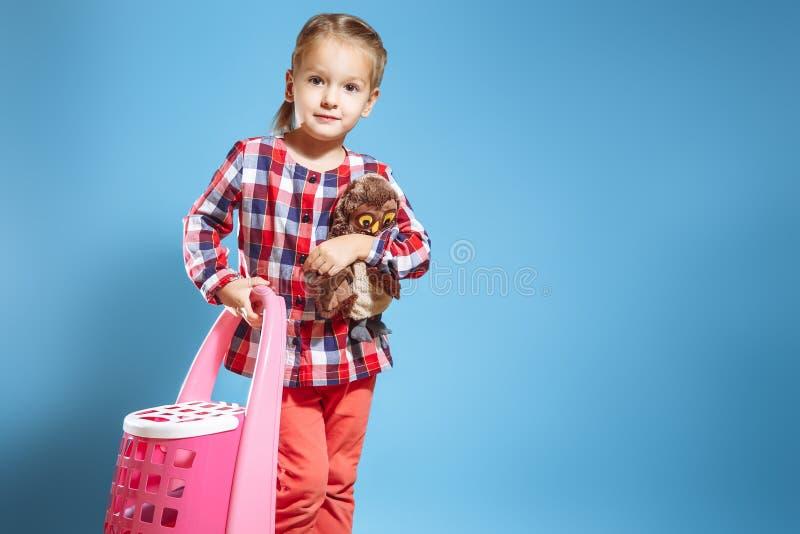 Liten flicka med en resväska och en favorit- leksak på en blå bakgrund för dublin för bilstadsbegrepp litet lopp översikt arkivfoto
