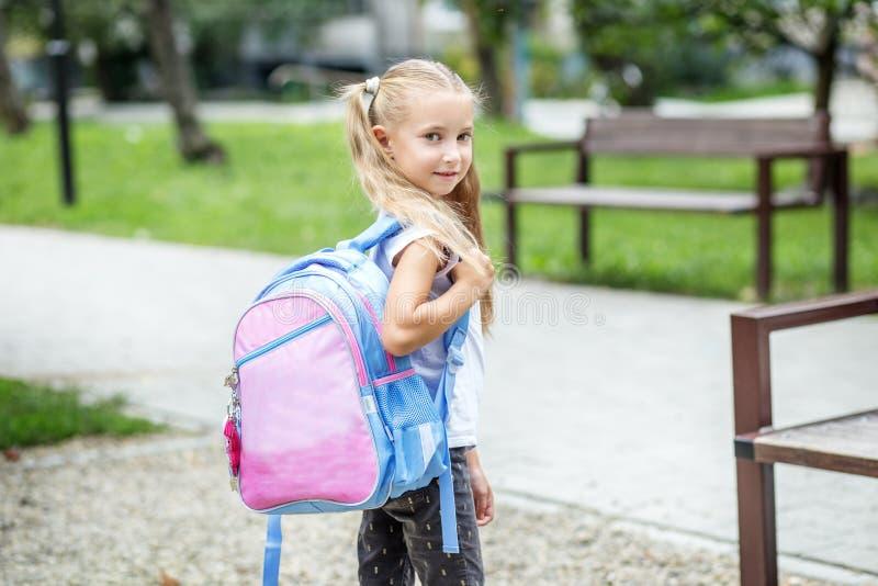 Liten flicka med en skolaryggsäck Begreppet av skolan, studie, utbildning, kamratskap, barndom arkivfoton