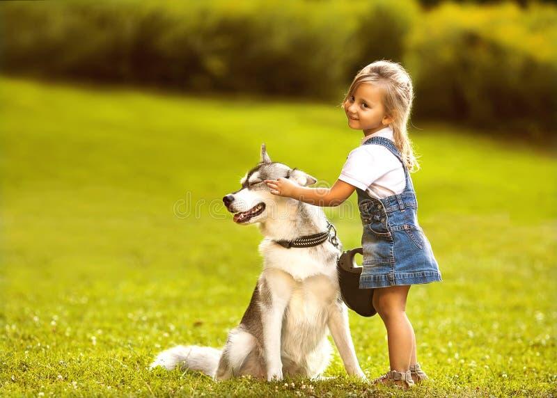 Liten flicka med en skrovlig hund royaltyfri foto
