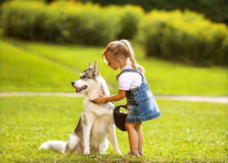 Liten flicka med en skrovlig hund royaltyfria bilder