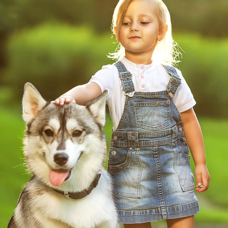 Liten flicka med en skrovlig hund arkivbild