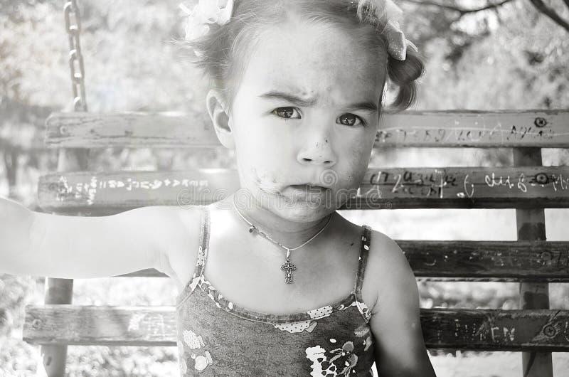 Liten flicka med en smutsig framsida och pilbågar på en gunga royaltyfri bild